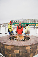 MacKenzie Ryan, Jack, and Avie warm by the outdoor fire at the Giant Steps Lodge after riding at Brian Head, Utah.