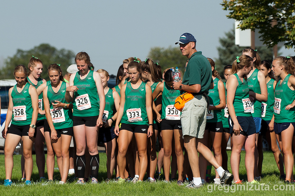 Long time Mountain View volunteer Bruce Walters and the JV team (L to R: Mariah Simpson, Kaitlyn Lange, Jessica Statsney, Abby Alexander, Bella Colson, Sam Johnston, Savannah Steele, Megan Laub, Morgan Holbrook) before the start of the Roger Curran Invitational Junior Varsity race at West Park in Nampa, Idaho on September 8, 2012.