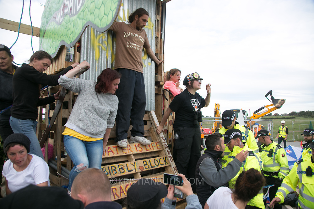 13 local activists locked themselves in specially made arm tubes to block the entrance to Quadrilla's drill site in New Preston Road, July 03 2017, Lancashire, United Kingdom. Police forcing protestors away fro the gates. Activists up the make-shift tower prevent police form clearing that. The 13 activists included 3 councillors; Julie Brickles, Miranda Cox and Gina Dowding and Nick Danby, Martin Porter, Jeanette Porter,  Michelle Martin, Louise Robinson,<br /> Alana McCullough, Nick Sheldrick, Cath Robinson, Barbara Cookson, Dan Huxley-Blyth. The blockade is a repsonse to the emmidiate drilling for shale gas, fracking, by the fracking company Quadrilla. Lancashire voted against permitting fracking but was over ruled by the conservative central Government. All the activists have been active in the struggle against fracking for years but this is their first direct action of peacefull protesting. Fracking is a highly contested way of extracting gas, it is risky to extract and damaging to the environment and is banned in parts of Europe . Lancashire has in the past experienced earth quakes blamed on fracking. (photo by Kristian Buus/In Pictures via Getty Images)