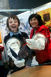 """NO REPRO FEE: Dublin Thursday 12th January 2012: Shirts which never wrinkle, paper from apples and rear windows with programmable lights - the EU stand at the BT Young Scientist gave visitors a chance to check out the latest EU-funded research and to chat with EU research staff about careers and the work they do. Pictured (l-r) at the European Commission stand was Oisin Martyn from St Patricks Classical School, Navan with Barbara Nolan, Director of the European Commission Representation in Ireland, Dundalk demonstrating the """"glove box"""" which helps users to learn about the EU Joint Research Centre's work on nuclear research. Glove boxes are normally used in nuclear facilities and laboratories for the handling and storage of radioactive material. Picture Conor McCabe Photography.For more information contact Joan Flanagan 087/2544346"""