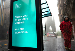 Edinburgh, Scotland, UK. 13 June 2020. On a foggy wet Saturday afternoon the streets of Edinburgh city centre remain very quiet and shops and businesses remain closed. Lockdown is expected to be relaxed next month. Video display screen at bus stop displays thank you message to care home workers.   Iain Masterton/Alamy Live News