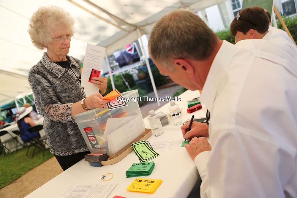 """Patti Prather, left, places her bet with Donnie Head using her """"Derby Dollars"""" at saturday's annual Derby Day fund raisier."""