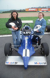 Two female racing car drivers standing on track next to racing car holding crash helmets,