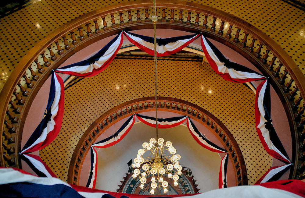 Arizona State Capitol Rotunda From Third Floor in Phoenix, Arizona<br /> The circular rotunda of the Arizona State Capitol in Phoenix is decorated with red, white and blue banners and plunges past a chandelier and four levels to the mosaic state seal on the first floor.  Surrounding it are exhibits explaining the history of the territory, state and politics.