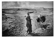 15..Old woman leads donkey across high plateau west of Kawkaban.  Because this rocky plateau receives rain, local villages farm the desolate table land.