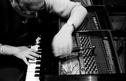 Piano tuner Paul Chrimes, a member of the Association of Blind Piano Tuners, working at the keyboard of an instrument at the Grand Theatre, Wolverhampton, England, UK.