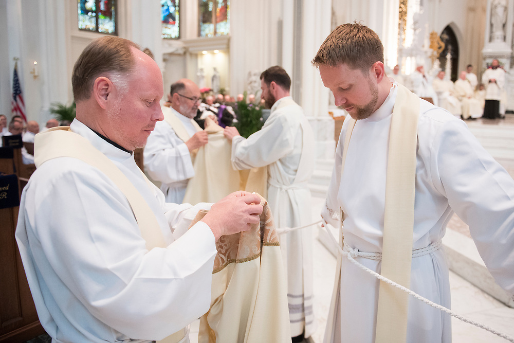 DENVER, CO - MAY 13: Daniel Ciucci (R) prepares to receive his vestments during his ordination to the priesthood at the Cathedral Basilica of the Immaculate Conception on May 13, 2017, in Denver, Colorado. (Photo by Daniel Petty/for Denver Catholic)
