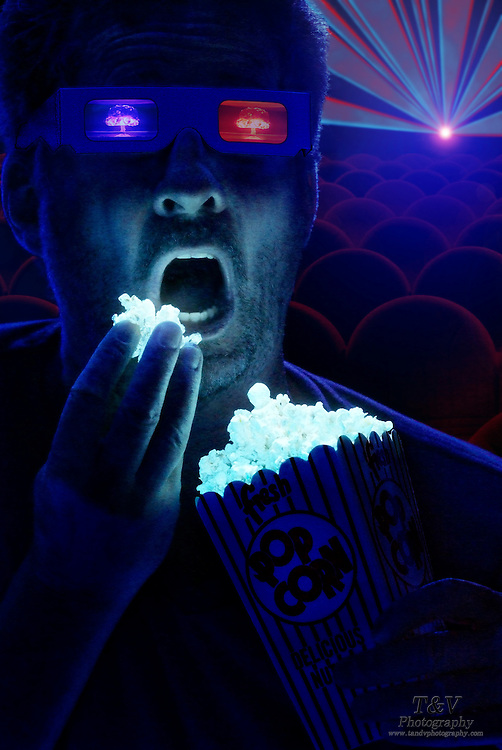A man in a theatre eats glowing popcorn while watching a 3D movie.Black light