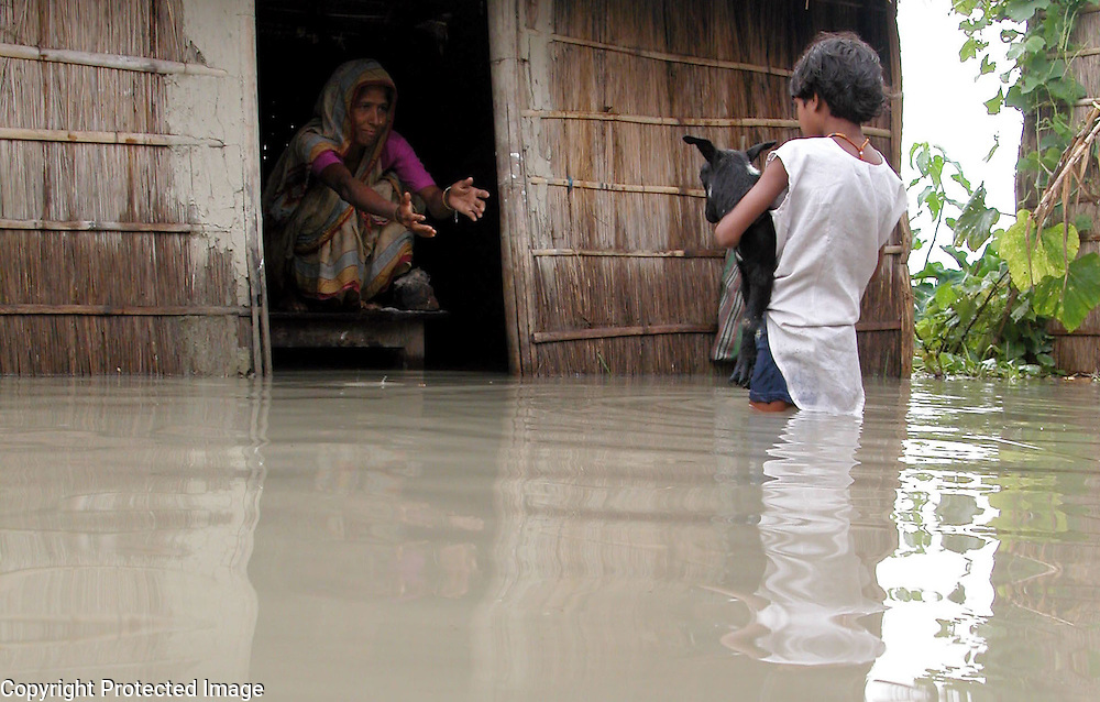 An unidentified girl carries her pet, goat through floodwaters at a safer place after their pet-house or goat-shed is inundated by floodwater at Dhrmashala village, about 319 kilometers southwest of Gauhati, the capital city of Northeastern Indian state, Assam, Sunday, June 27, 2004..Floodwaters of the Asia'a one of the largest river, Brahmaputra and its 35 tributaries have affected more than one million in all of Indian subcontinent and disrupted communication in many parts of the India and Bangladesh, sources said. (AP Photo/ Shib Shankar Chatterjee)
