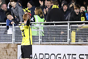 Harrogate Town midfielder Michael Woods (21) celebrates in front of the Harrogate Town fans during the Vanarama National League match between FC Halifax Town and Dover Athletic at the Shay, Halifax, United Kingdom on 17 November 2018.
