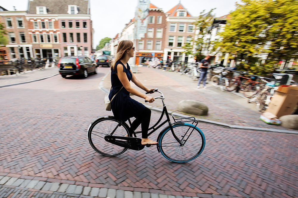 In Utrecht rijdt een jonge vrouw op een swapfiets, een nieuw huurconcept.  De swapfiets is te huur voor een klein bedrag per maand, bij een defect wordt de fiets binnen 12 uur gerepareerd of omgeruild voor een andere. In tegenstelling tot andere huurfietsen deel je de fiets niet met meerdere gebruikers. De fietsen zijn te herkennen aan de blauwe voorband.<br /> <br /> In Utrecht a woman cycles on a swapbike. The swapbike is a rental concept. For a small amount per month the bicycle can be rented. If there is a defect, the company fixes the bike within 12 hours or swaps it for another bike. You don't share the bike with others, as with other common rental bikes.