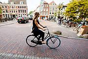 In Utrecht rijdt een jonge vrouw op een swapfiets, een nieuw huurconcept.  De swapfiets is te huur voor een klein bedrag per maand, bij een defect wordt de fiets binnen 12 uur gerepareerd of omgeruild voor een andere. In tegenstelling tot andere huurfietsen deel je de fiets niet met meerdere gebruikers. De fietsen zijn te herkennen aan de blauwe voorband.<br /> <br /> In Utrecht a woman cycles on a swapbike. The swapbike is a rental concept. For a small amount per month the bicycle can be rented. If there is a defect, the company fixes the bike within 12 hours or swaps it for another bike. You don&rsquo;t share the bike with others, as with other common rental bikes.