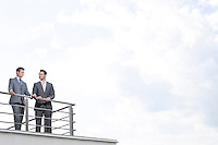 Businessmen standing at terrace railings against cloudy sky