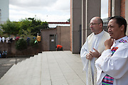 Father Paulo waits to greet worshipers outside the front of the chruch, Our Lady Of Peace, at Missao Paz, São Paulo, Brazil.<br /> <br /> Missao Paz provides advice and support on employment, health, family, community and education. They also have residential quarters where people can stay when they have no where else. <br /> <br /> Their mission is to welcome, understand, integrate and celebrate the lives of immigrants and refugees, dreaming of a universal citizenship.