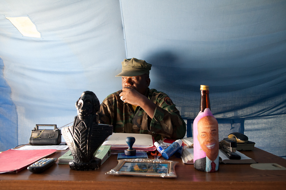 "Sergeant Chery Samson, talks on a phone at his desk in a small tent in a densely populated neighborhood in Petion-Ville. On Samson's desk is a bust of Toussaint L'Ouverture (who led the Haitian slave revolt and defeated Napoleon) and a rum bottle with a President Michel Martelly's face painted on it. Samson says that he is in charge of all of the troops in Haiti. Samson keeps a copy of the Haitian constitution on his desk and qoutes article 267-3 which says ""(the government) does not have the right to decommission the military... the government does not have the right to put the military on leave"" Samson who was in the Haitian army from 1980 to 1995 says ""even though we didn't have resources we've always been the military and have always defended the interests of the military and the country"" and ""January 12th, the earthquake happened I was saving an old person's life and a house collapsed on me and I lost my hand. When I was in the hospital several commanders came and visited me and we decided that we needed to start getting organized and set up offices to control the whole army and we started re-mobilizing. .We are waiting for Michel Martelly to name the minister of defense and the major for the army. We are all in little groups and at that time we'll come together."""