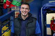 AFC Wimbledon attacker Tommy Wood (22) smiling whilst stood at side of pitch during the The FA Cup match between AFC Wimbledon and Doncaster Rovers at the Cherry Red Records Stadium, Kingston, England on 9 November 2019.