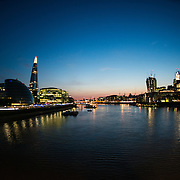 The London city skyline at dusk, as seen from the Tower Bridge. Queen's Walk is at left, with the half-dome of the London City Hall and The Shard standig tall behind that.