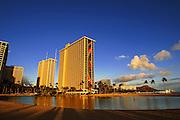 The Rainbow Tower of the Hilton Hawaiian Village glows as the sun sets.
