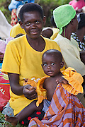 Magret with baby Carolyne (1 year old) Women from Kitahurira, the only Batwa tribe settlement in Mpungu district, wait with their children to attend the Bwindi Community Hospital outreach clinic. The mothers and children receive nutrition information and vaccinations from the hospital nurse.  Bwindi Community Hospital provides different outreach clinics everyday for the surrounding area around Buhoma. The Mpungu district is on the edge of the Bwindi Impenetrable Forest, Western Uganda.