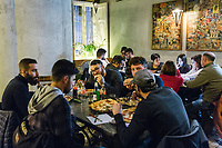 "NAPLES, ITALY - 8 DECEMBER 2017: Customers eat pizza here at Pizzeria Gino Sorbillo in Naples, Italy, on December 8th 2017.<br /> <br /> On Thursday December 7th 2017, UNESCO added the art of Neapolitan ""Pizzaiuolo"" to its list of Intangible Cultural Heritage of Humanity.<br /> <br /> The art of the Neapolitan 'Pizzaiuolo' is a culinary practice comprising four different phases relating to the preparation of the dough and its baking in a wood-fired oven, involving a rotatory movement by the baker. The element originates in Naples, the capital of the Campania Region, where about 3,000 Pizzaiuoli now live and perform. Pizzaiuoli are a living link for the communities concerned. There are three primary categories of bearers – the Master Pizzaiuolo, the Pizzaiuolo and the baker – as well as the families in Naples who reproduce the art in their own homes. The element fosters social gatherings and intergenerational exchange, and assumes a character of the spectacular, with the Pizzaiuolo at the centre of their 'bottega' sharing their art.<br /> <br /> In Naples, pizza makers celebrated the victory by giving away free pizzas."