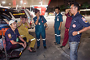 """Oct. 1, 2009 -- BANGKOK, THAILAND: SOMJIT JANGJOHOR, a Thai actor, singer and boxer on Thailand's Olympic team, RIGHT, and volunteers from Poh Teck Tung wait in a gas station parking lot for a call. Several Thai actors and pop singers do volunteer work with the organization.  The 1,000 plus volunteers of the Poh Teck Tung Foundation are really Bangkok's first responders. Famous because they pick up the dead bodies after murders, traffic accidents, suicides and other unplanned, often violent deaths, they really do much more. Their medics respond to medical emergencies, from minor bumps and scrapes to major trauma. Their technicians respond to building collapses and traffic accidents with heavy equipment and the """"Jaws of Life"""" and their divers respond to accidents in the rivers and khlongs of Bangkok. The organization was founded by Chinese immigrants in Bangkok in 1909. Their efforts include a hospital, college tuition for the poor and tsunami relief.    Photo by Jack Kurtz / ZUMA Press"""