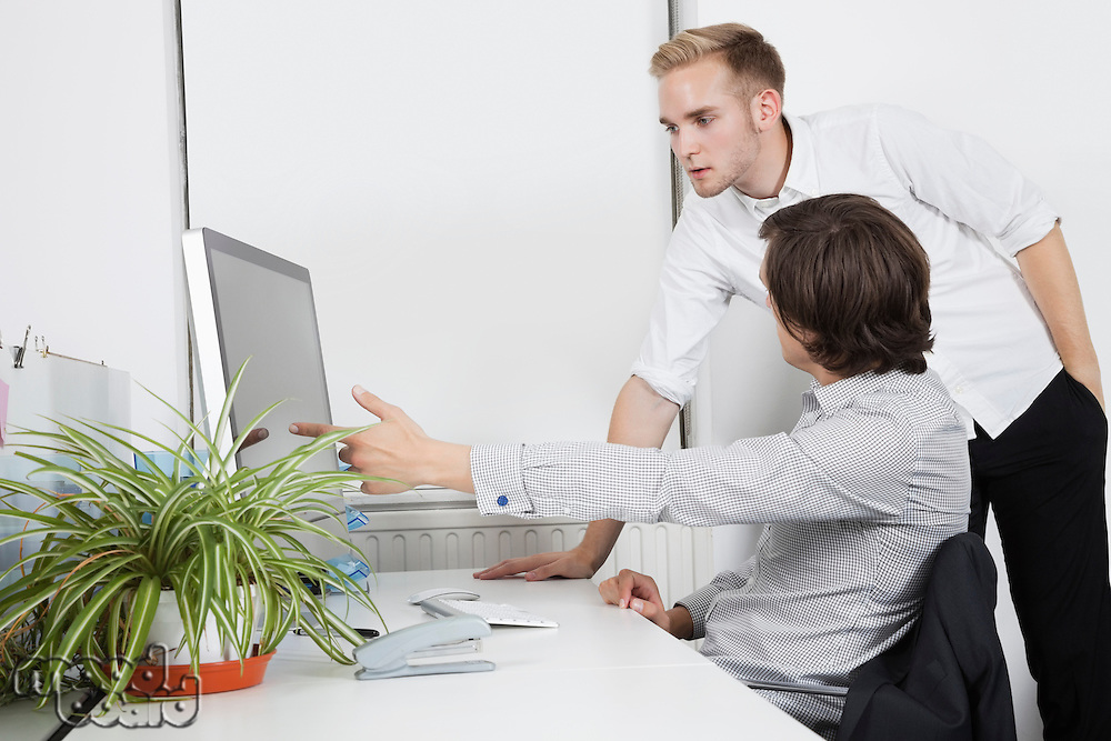 Businessman showing computer screen to coworker at desk