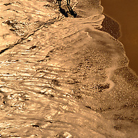 Aerial of a couple waling on the beach with waves crashing at their feet.
