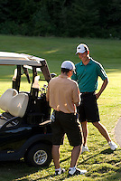 Men compare scores after a golf game as they stand beside the golf cart, Whistler Golf Course, Whistler, BC Canada.