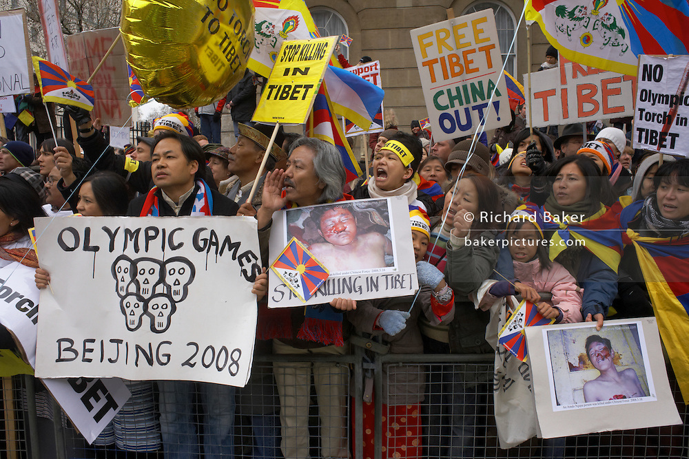 Standing behind barriers opposite Prime Minister Brown's Downing Street in Whitehall, the heart of Britain's governmental district in Westminster, some of the thousands of pro-Tibet protesters angrily shout their messages to 80 torchbearing personalities who ran 31 miles through the UK capital's streets. We see them holding images of dead Tibetans, killed by Chinese forces during the most recent crackdown in Lhasa and holding placards with anti-Chinese messages. Amid chaotic scenes across London and Paris where mass-arrests and civil disobedience marked what was planned as a  pre-Olympic carnival, the IOC's event proved a disaster for Chinese organisers. 37 were arrested but these facts were blanked from official TV screens which showed only the calm personlities who carried in turn the Olympic flame.