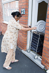 Older woman manoeuvring shopping trolley through the front door of her house,