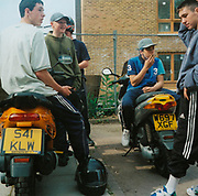 Group of boys sitting on motorbikes and smoking