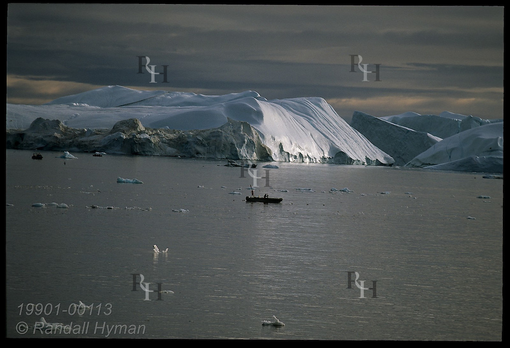 Icebergs calved from Sermeq Kujalleq glacier clog Disko Bay where Ilulissat Kangerlua Icefjord meets sea, dwarfing boat; Greenland