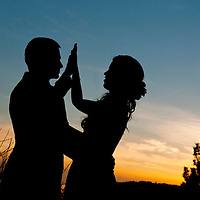 Travis and Amy high five at sunset after their Vancouver Island wedding.