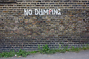 No Dumping writing painted on an urban brick wall in the south London borough of Lewisham, SE5.