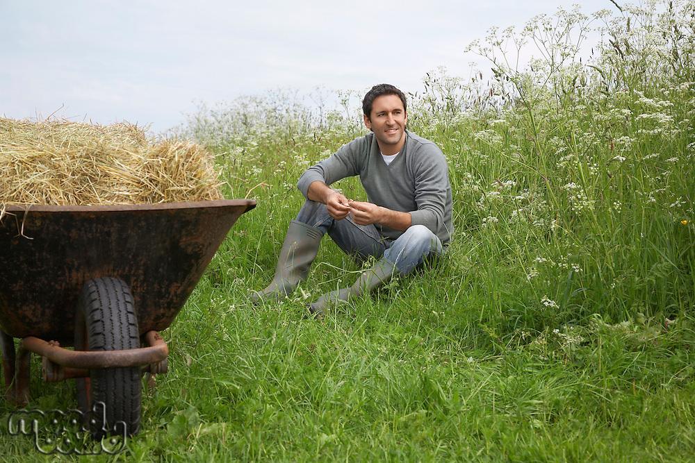 Man sitting beside wheelbarrow with hay in field portrait