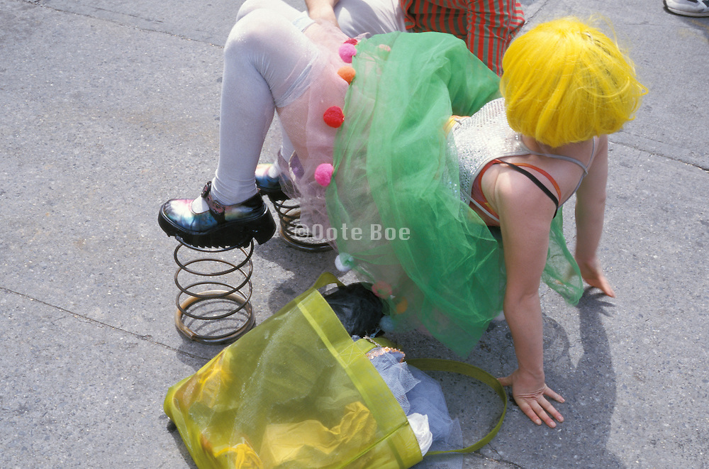 Girl in costume trying to get up with springs on her feet