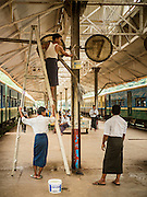 26 OCTOBER 2015 - YANGON, MYANMAR: Maintenance workers wash the platform signs used on the Circular Train line in the Yangon Central Station. The Yangon Circular Railway is the local commuter rail network that serves the Yangon metropolitan area. Operated by Myanmar Railways, the 45.9-kilometre (28.5mi) 39-station loop system connects satellite towns and suburban areas to the city. The railway has about 200 coaches, runs 20 times daily and sells 100,000 to 150,000 tickets daily. The loop, which takes about three hours to complete, is a popular for tourists to see a cross section of life in Yangon. The trains run from 3:45 am to 10:15 pm daily. The cost of a ticket for a distance of 15 miles is ten kyats (~nine US cents), and for over 15 miles is twenty kyats (~18 US cents).    PHOTO BY JACK KURTZ