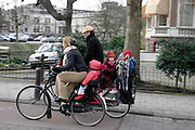 Een man en vrouw fietsen met jonge kinderen achterop door Amsterdam.<br /> <br /> A man and woman are cycling with young childs on the back in Amsterdam