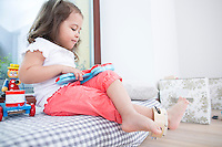 Cute girl playing toy guitar at home