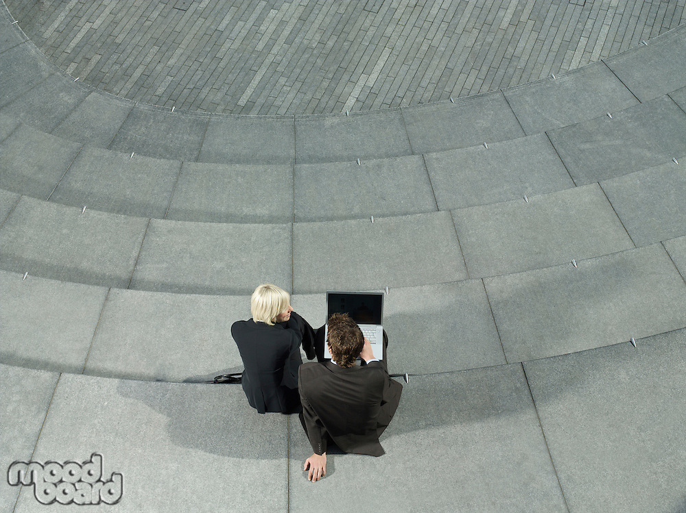 Business man and woman sitting on spiral stairs using laptop elevated & back view