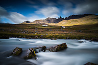 A river flowing in front of the farm Hraun in Valley Öxnadalur, North Iceland. In background rays of light hit Mount Drangafjall. The Peak Hraundrangi (1075m) was first climbed in 1956.