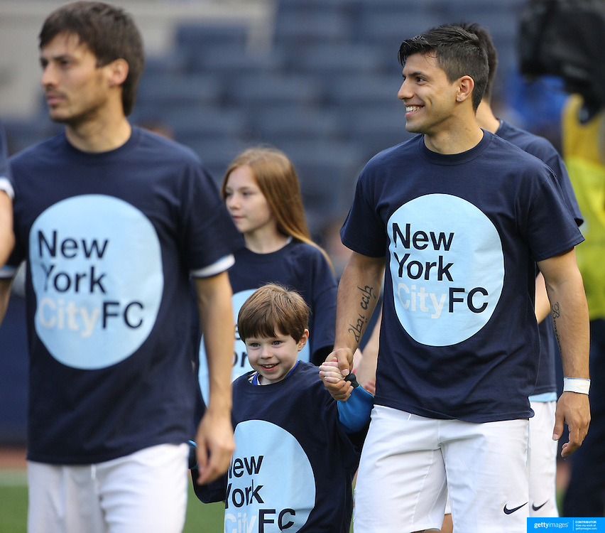 Manchester City players including David Silva (left) and Sergio Aguero wearing New York City FC shirts as they are accompanied by children onto the pitch before the Manchester City V Chelsea friendly exhibition match at Yankee Stadium, The Bronx, New York. Manchester City won the match 5-3. New York. USA. 25th May 2012. Photo Tim Clayton
