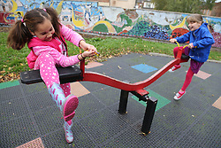 Two girls on seesaw in urban park