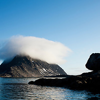 Norway, Svalbard, Spitsbergen Island, Sea fog covers peak of small island at mouth of Fuglefjorden on summer evening