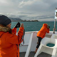 Two women photograph from the bow of the National Geographic Orion while exploring in Royal Bay on the north coast of South Georgia Island.