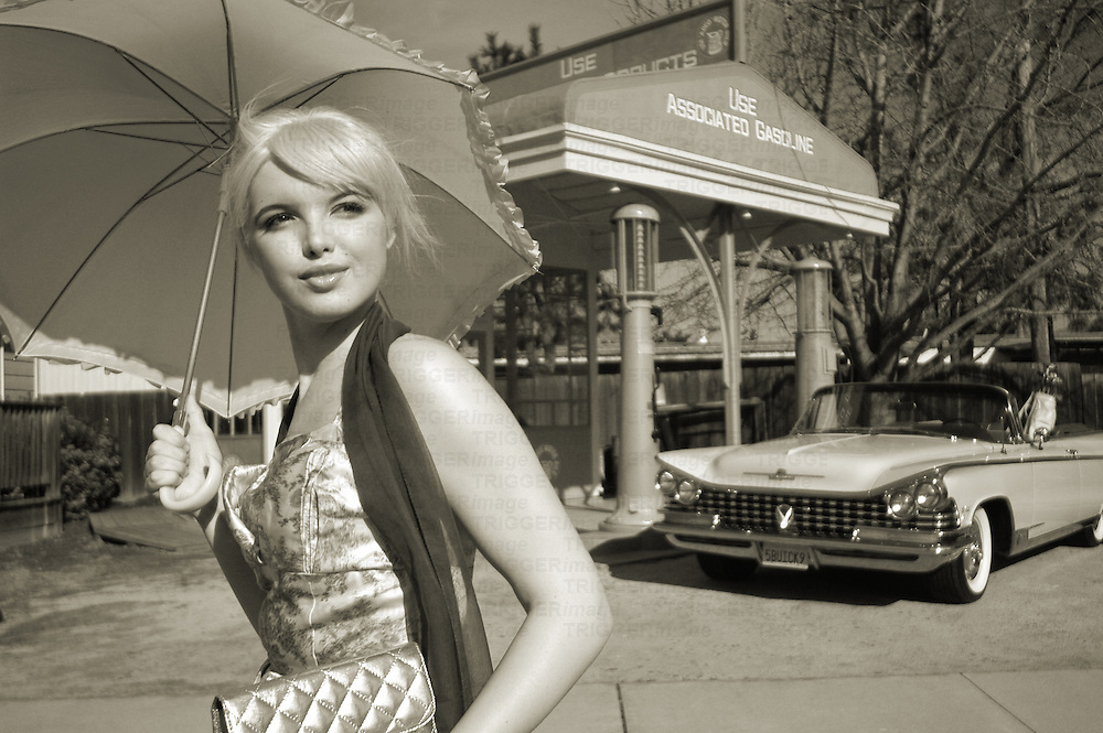 A young model holding a sun shade near a 60's car