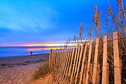 Sandfence and sea oats leads the eye out to a single fishermen starting his day on the Outer Banks at the break of day.