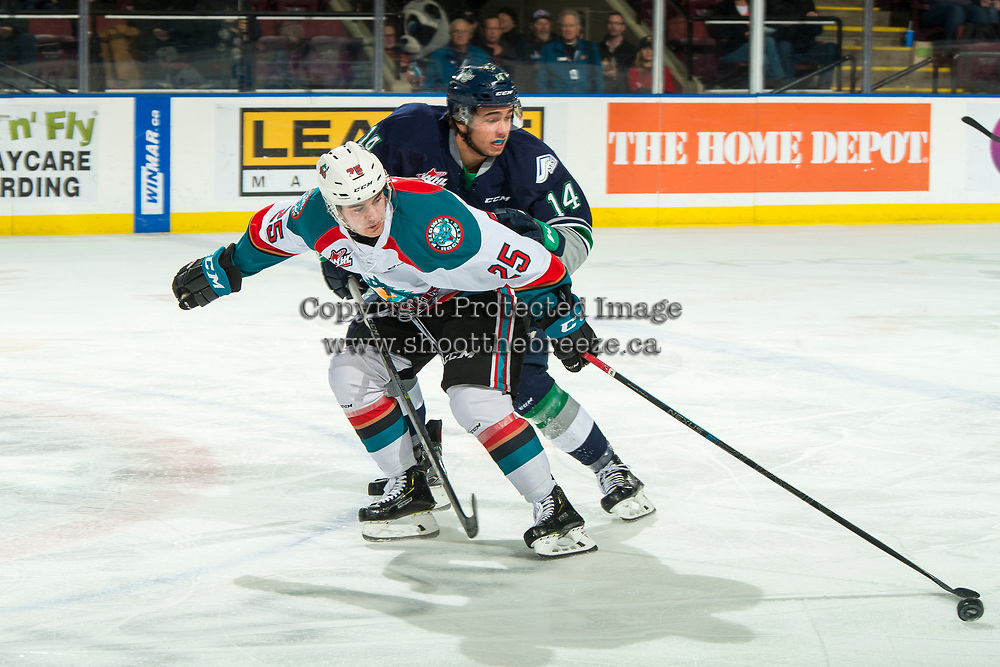 KELOWNA, CANADA - JANUARY 30:  Tyler Carpendale #14 of the Seattle Thunderbirds back checks Kyle Crosbie #25 of the Kelowna Rockets as he skates with the puck during first period on January 30, 2019 at Prospera Place in Kelowna, British Columbia, Canada.  (Photo by Marissa Baecker/Shoot the Breeze)