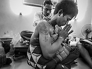 "07 MARCH 2015 - NAKHON CHAI SI, NAKHON PATHOM, THAILAND: A man prays after getting a new tattoo at the Wat Bang Phra tattoo festival. Wat Bang Phra is the best known ""Sak Yant"" tattoo temple in Thailand. It's located in Nakhon Pathom province, about 40 miles from Bangkok. The tattoos are given with hollow stainless steel needles and are thought to possess magical powers of protection. The tattoos, which are given by Buddhist monks, are popular with soldiers, policeman and gangsters, people who generally live in harm's way. The tattoo must be activated to remain powerful and the annual Wai Khru Ceremony (tattoo festival) at the temple draws thousands of devotees who come to the temple to activate or renew the tattoos. People go into trance like states and then assume the personality of their tattoo, so people with tiger tattoos assume the personality of a tiger, people with monkey tattoos take on the personality of a monkey and so on. In recent years the tattoo festival has become popular with tourists who make the trip to Nakorn Pathom province to see a side of ""exotic"" Thailand.   PHOTO BY JACK KURTZ"