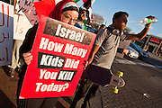 31 JANUARY 2011 - TEMPE, AZ: A woman carries a sign supporting Palestinian rights while a man waits to cross a street in Tempe, AZ, Monday. About 200 people marched through central Tempe, AZ, near the Arizona State University campus Monday afternoon. The rally was organized by the Arab American Association of Arizona in solidarity with the ongoing pro-democracy rallies and demonstrations in Egypt and other Arab countries.    Photo by Jack Kurtz